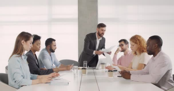 Mad male boss yelling at multiethnic group of employees and finishing corporate meeting. Male chief is unsatisfied with bad work of employeers. Concept of work, nervous breakdown.