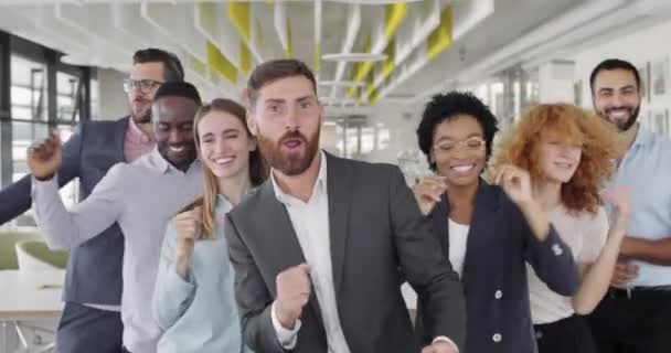 Group of happy multi ethnic business coworkers celebrating successful contract. Front view of cheerful mixed male and female office workers dancing, rejoicing and having fun together.