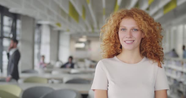 Confident millennial businesswoman in suit turning head to camera and smiling. Young caucasian female leader office worker standing in modern office. Portraits. Blurred background.