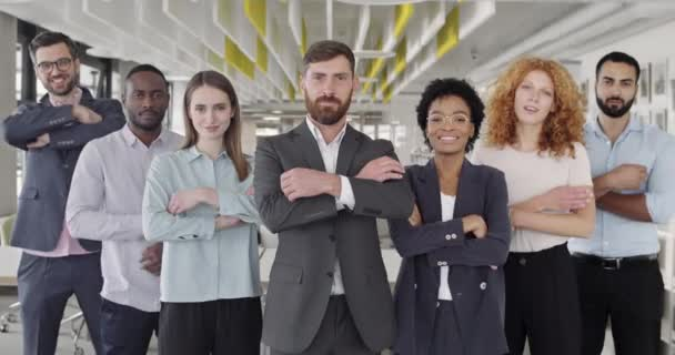 Positive multiracial company staff standing and crossing hands in office. Group of successful mixed workers with ther boss looking to camera and smiling. Concept of team portrait.