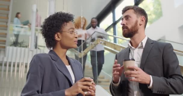 Man and woman office workers having conversation and standing with coffee paper cups. Coworkers of diverse ethnicity discussing project in free time chatting and smiling in office hall.
