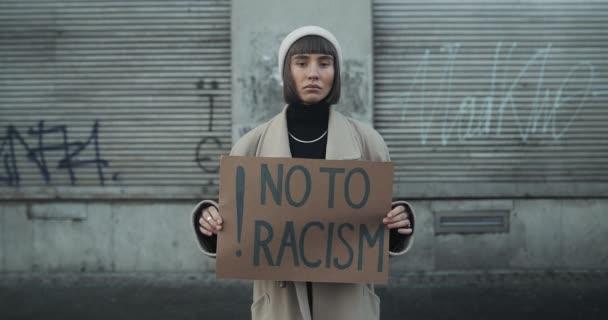 Ženská tisíciletá podpora lidských práv a žádná rasistická kampaň. Studentka drží plakát proti rasismu, zatímco stojí na prázdné ulici. Koncept rovných lidských práv a rasismu.