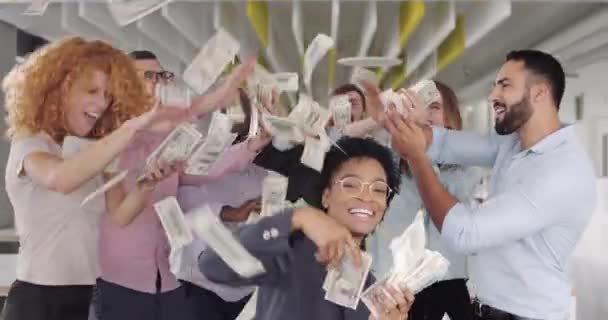Close up of smiling staff dancing while throwing money at modern office. Team of young diverse coworkers having fun, jumping, rejoicing victory at work space. Concept of successful business.