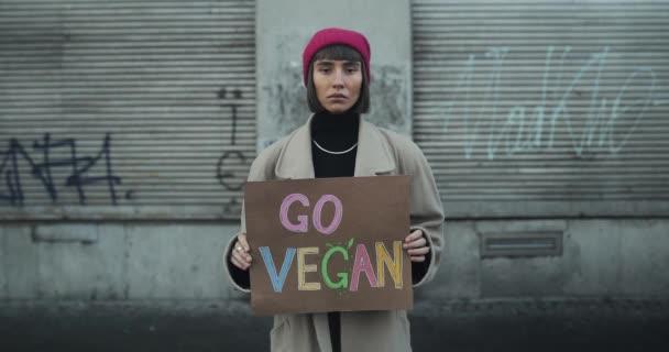 Mladá dívka s cedulí Go vegan stojící na prázdné ulici a dívající se do kamery. Ženský hipster propagující vegetariánství a zdravý životní styl. Koncept Go Green Go Vegan a Eco.