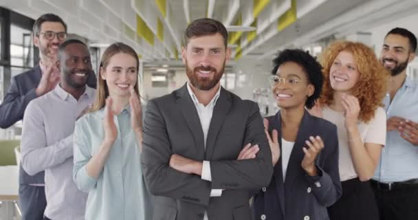 Friendly mixed ethnic office workers applauding and smiling to their male boss. Portrait of office workers group congratulating their ceo executive with success. Concept of work, victory.