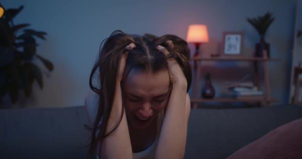 Detailní záběr dívky v depresi sedící na pohovce a držící hlavu rukama. Rozrušená mladá žena zažívá emocionální stres a hlasitě pláče. Domácí pozadí.