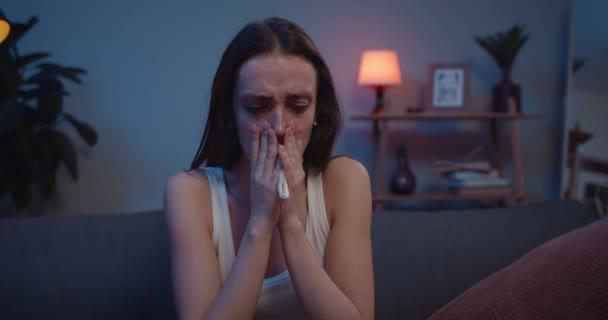 Mladá dívka s rozmazaným make-upem sedí na pohovce v slzách a cítí se špatně po smrti blízkého člověka. Přední pohled na ženu tisícileté v depresi pláče a zakrývá tvář s rukama .