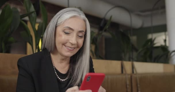 Close up of smiling gray heared old woman using smartphone while sitting in cafe. Happy female businessowner looking at mobile phone and touching screen . Concept of tech and communication.