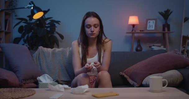 Přední pohled nešťastné dívky sedící na pohovce a držící papírový kapesník. Mladá žena v depresi pláče a dívá se do kamery. Domácí pozadí. Pojetí pocitů a emocí.