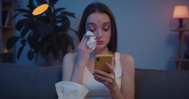 Detailní záběr mladé ženy, jak si otírá slzy z obličeje papírovou kapesníčkem, zatímco se dívá na obrazovku telefonu. Rozrušená dívka nemůže uvěřit špatné zprávy čtení na svém smartphonu a pláč.