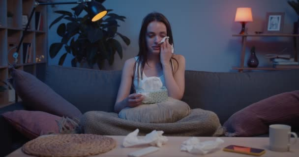 Front view of young upset girl sitting on sofa and using paper tissues and blowing nose. Depressed millennial woman holding box of handkerchief on her knees wiping away tears.