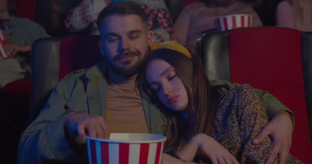 Vorderansicht des hübschen Mädchens, das während des Films auf der Schulter ihres Freundes schläft. Bärtiger Typ isst Popcorn und umarmt Freundin, schaut sie an und lächelt ins Kino.