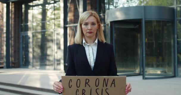 Female employee in 30s getting fired during corona crisis . Unhappy woman showing carton banner while standing at street and looking to camera at business district. Concept of unemployment.