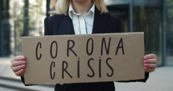Crop view of female employee showing carton banner with corona crisis writing. Jobless woman in formal clothes standing at street after dismiss. Concept of unemployment.