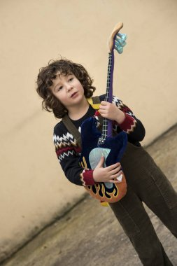 boy playing and experimenting with a toy guitar with striking colors