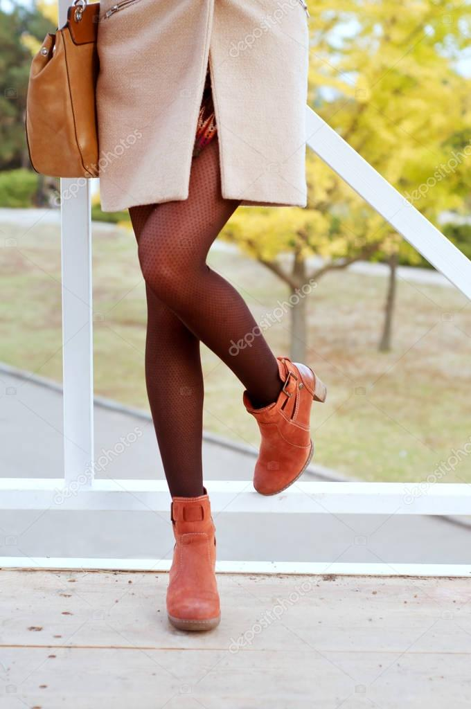 Woman wearing black tights and suede orange boots dressed in coa