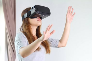 Young woman wearing virtual reality glasses at home.