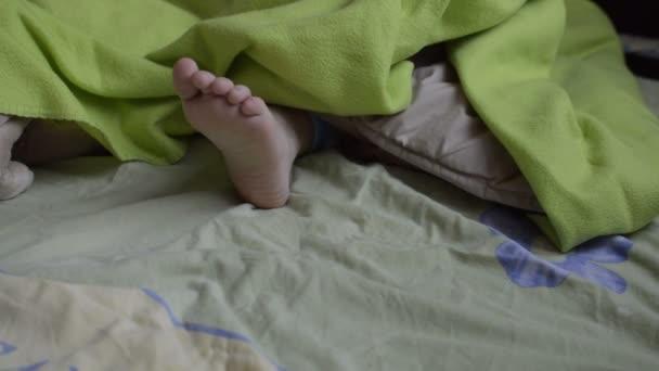 piedi del bambino sotto la coperta verde