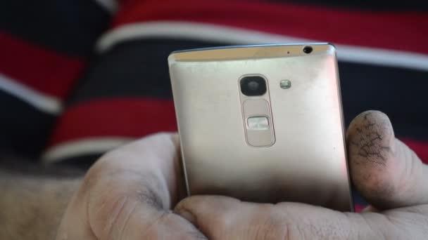 Der Mann blickt auf das Smartphone-Display und blättert durch die Seiten. Nahaufnahme