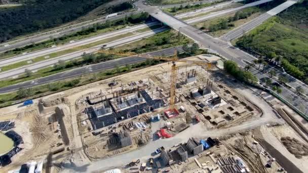 Luftaufnahme einer neuen Baustelle mit Kran und Baumaterialien.