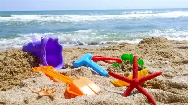 A tenger parton, homokozó készletet, a hullámok a háttérben
