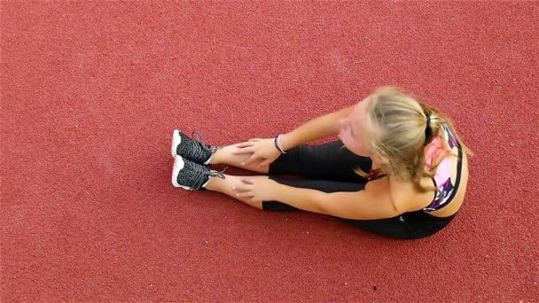 Pohled shora dospívající dívka sportovce strečink před spuštěním na stadionu, pomalý pohyb