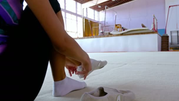 Gymnast putting on her shoes, preparing for training