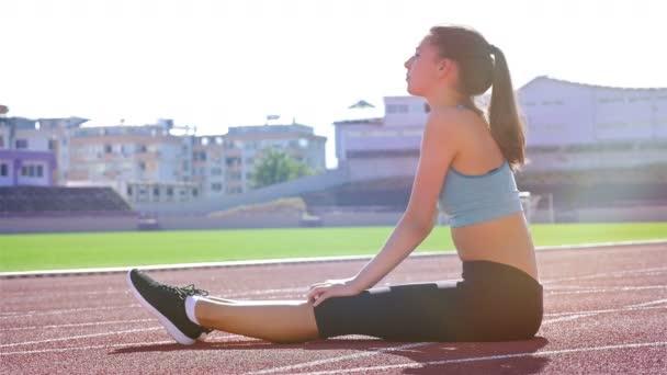 Sledování běžec atlet žena rozcvičení před spuštěním na stadionu
