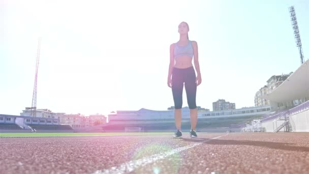 Track runner athlete woman warming up before running at a stadium, sun flare