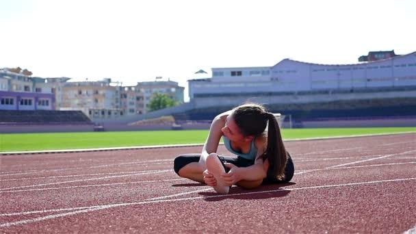 Tenere traccia di corridore donna atleta riscaldamento prima esecuzione a uno stadio, rallentatore