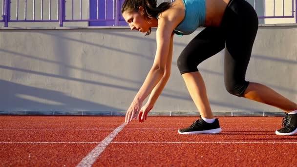 Sledování běžec žena položila ruce na startovní čáře, pomalý pohyb
