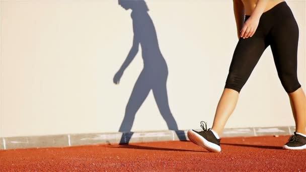 Sledování běžec žena a její stín na zdi chystá spustit, zpomalené