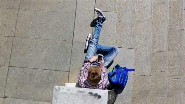 Top view of teenager boy with skateboard and backpack listening to music on smartphone