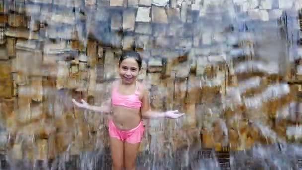 ecbd68d42b7c Cute little girl in swimsuit having fun under falling water before a stone  wall– stock footage