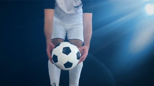 Fotbalista v botách uvedení nohu na míč, černé pozadí