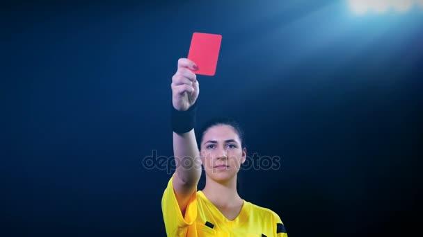 Nő Labdarúgás nemzetközi labdarúgó-játékvezető mutatja büntetés piros kártyát a fekete háttér, 4k