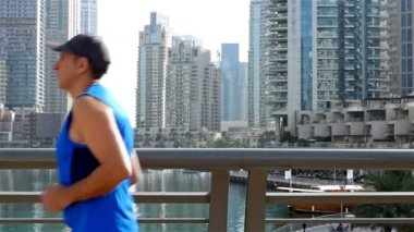 Athletic fitness man running jogging in Dubai Marina in the morning, slow motion
