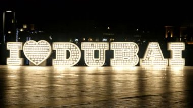 People passing by in front of lighted 'I love Dubai' logo at night, 4k