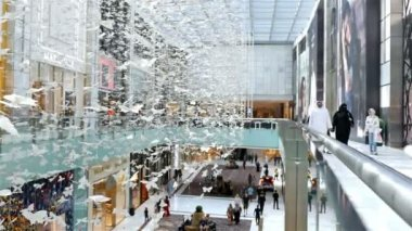 Shoppers people at Dubai Mall, the world's largest shopping mall, large butterfly art installation in front, 4k