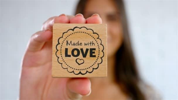 attraktive junge Frau mit liebevoll hergestelltem Stempel und Lächeln, 4k