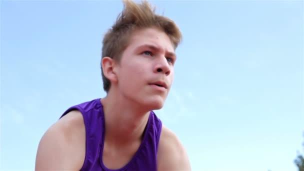 Nízký úhel pohledu trati běžec boy teenagera připravuje na startovní čáře, 4k