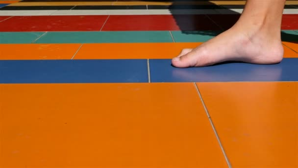 Woman bare feet walking on colorful tiles, freedom concept, 4k