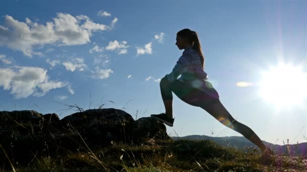 Low angle view of Woman on top of mountain stretching at Sunset view Hiker Girl celebrating life scenic nature landscape enjoying vacation travel adventure