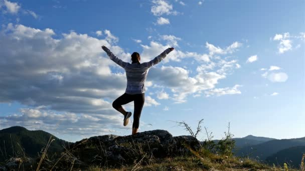 Woman exercising yoga on top of mountain at Sunset. Hiker Girl celebrating life scenic nature landscape enjoying vacation travel adventure, 4k