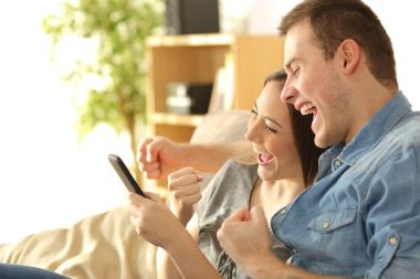 Excited couple checking content in a phone
