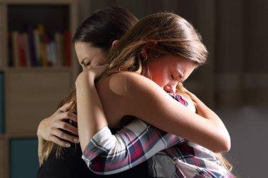 Two sad teens embracing at bedroom