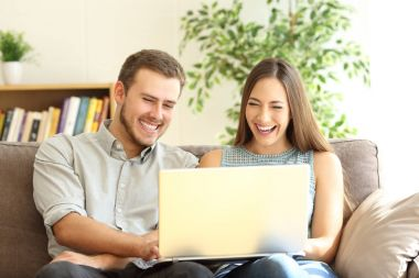 Couple laughing watching on line content in a laptop