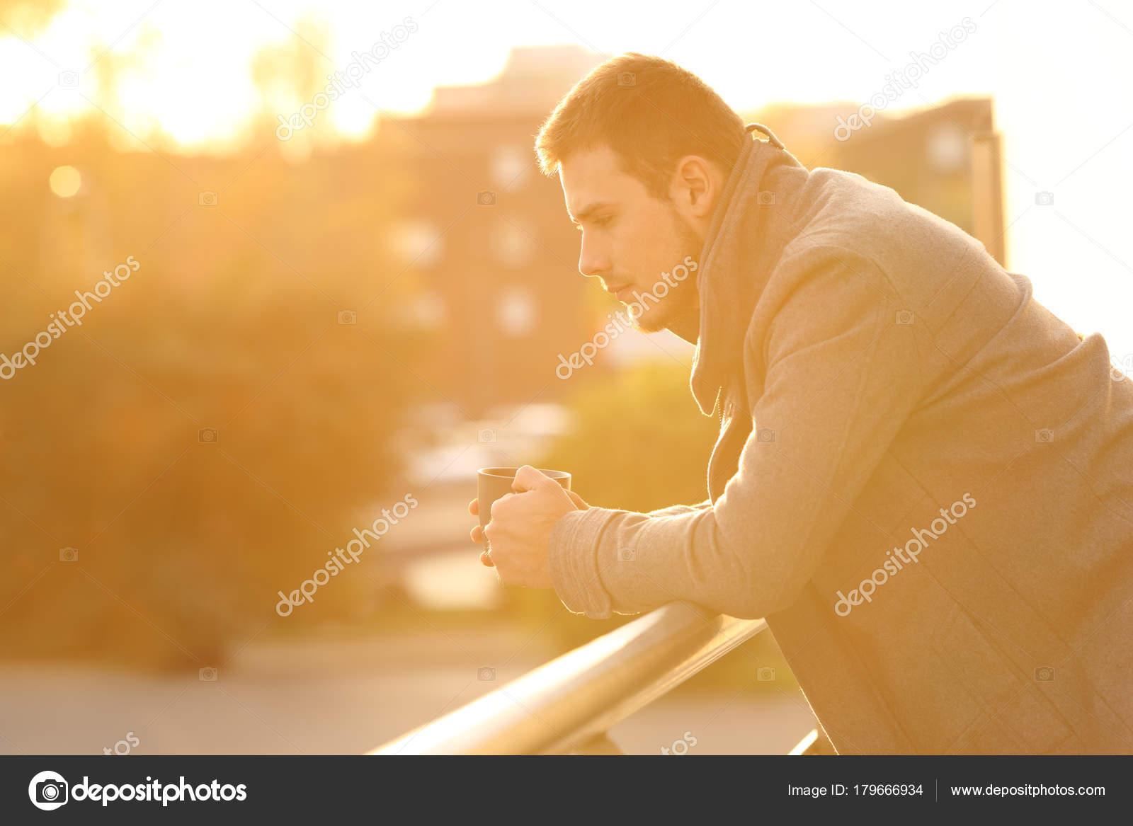 Een Winters Balkon : Trieste man op zoek naar beneden in een balkon in de winter