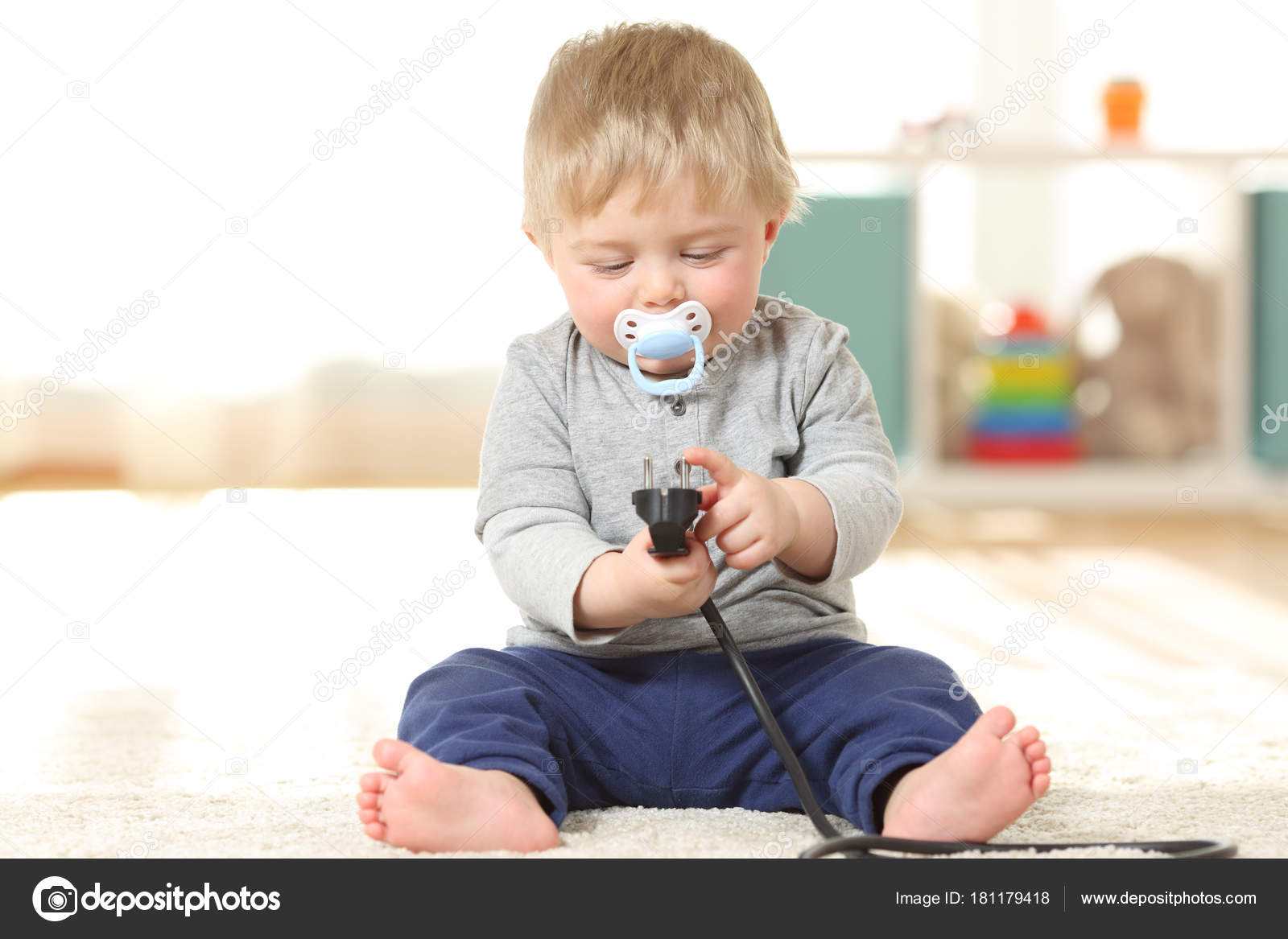 Fronf View Portrait Of A Baby In Danger Playing With An Electric Plug  Sitting On The Floor At Home U2014 Photo By AntonioGuillemF