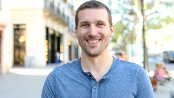 Přední pohled portrét šťastného dospělého muže hledícího na kameru na ulici
